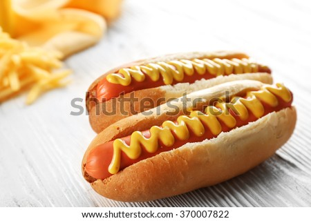 Hot dogs with cheese on wooden background - stock photo