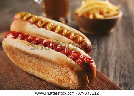 Hot dogs with fried potatoes on cutting board - stock photo