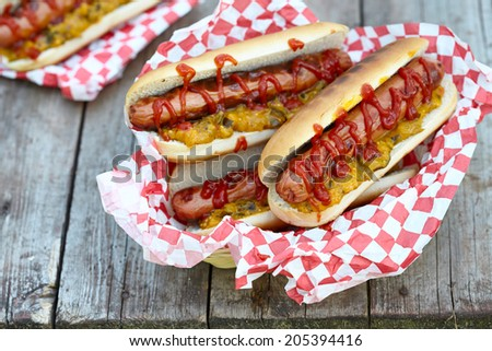 Hot dogs with ketchup and mustard relish for a picnic - stock photo