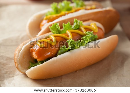 hot dogs with mustard on paper for lunch - stock photo