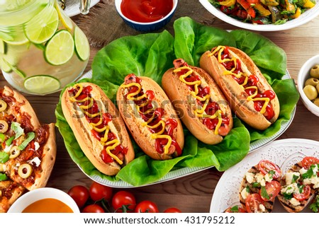 Hot Dogs with sausage, mustard and ketchup on lives salad - stock photo