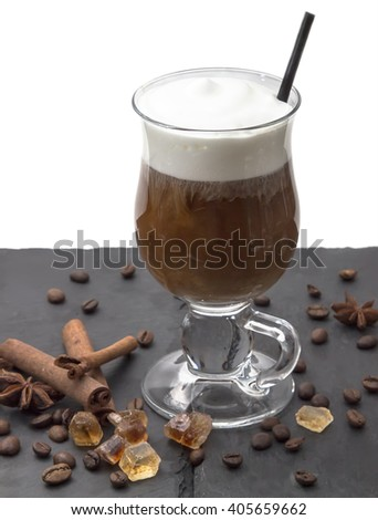 Hot drink in glass with milk foam - coffee latte, cappuccino, moccachino with tube, on the black table. Near the cinnamon sticks, anise and caramel sugar. - stock photo