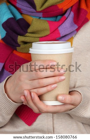 Hot drink in paper cup in hands close up - stock photo