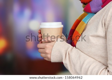 Hot drink in paper cup in hands on bright background - stock photo