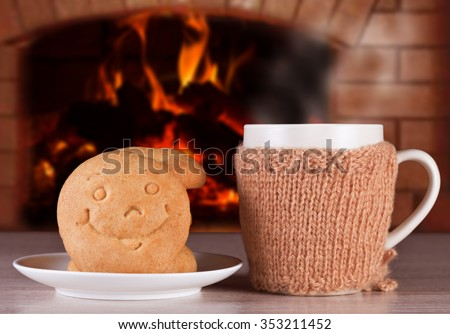 Hot drink with buns in the form of smiles to warm and positive mood on the background of a blazing fire in the oven - stock photo
