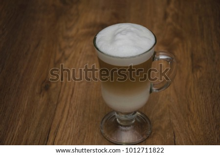 hot drink with coffee and milk, latte, cappuccino, in a beautiful glass glass, on a wooden table