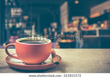 Hot espresso on the table with coffee shop background, vintage tone  - stock photo