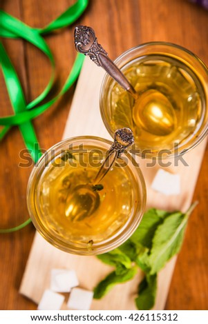 hot fresh tea with green mint and sugar on wooden background