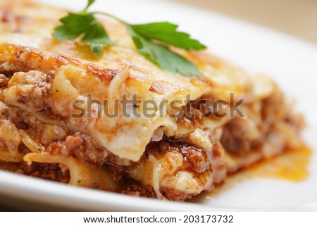 hot freshly made home lasagna, close up in plate with parsley leaf - stock photo