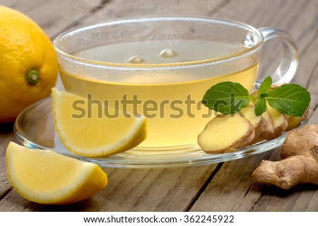 Hot ginger lemon tea with mint on wooden table
