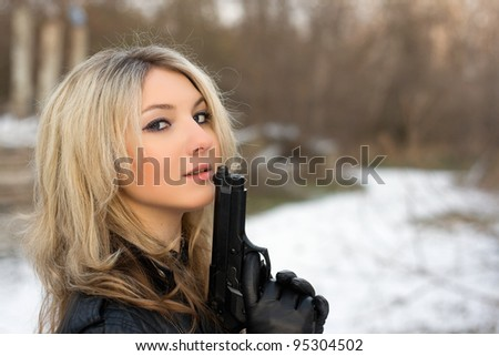 Hot girl holding a gun in winter forest - stock photo
