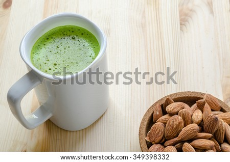 Hot green tea latte in lazy time with almonds nut - stock photo