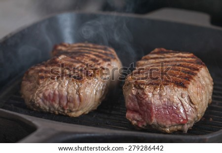 Hot Grilled beef steaks are cooking on grill pan - stock photo
