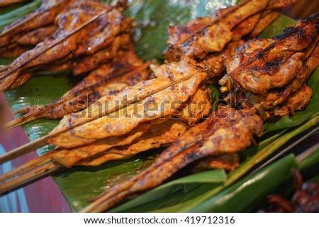Hot Grilling chickens plugged with bamboo on green leaf. smoked grill chicken barbecue, thai local food, traditional food Thailand - stock photo
