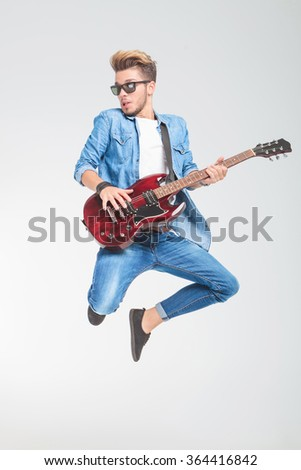 hot guy wearing sunglasses jumping in studio while playing guitar and looking away - stock photo