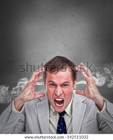 Hot headed business man shouting on grey background with copy space - stock photo