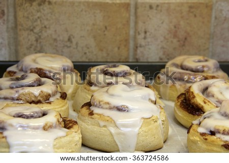 Hot homemade cinnamon rolls fresh out of the oven, frosting glaze dripping down the side of buns - stock photo