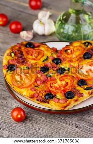 hot homemade pizza  heart with cheese, tomatoes, olives, sausage