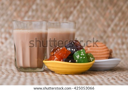 Hot Indian masala tea / masala chai / Teh Tarik with biscuits and halwa / mithai / sweets , Kerala India. Morning tea with refreshing Indian blend of black tea with milk and spices. - stock photo