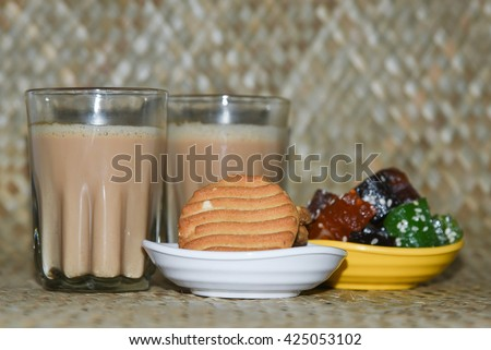 Hot Indian masala tea / masala chai / Teh Tarik with biscuits and halwa / mithai / sweets , Kerala India. refreshing Indian blend of black tea with milk and spices. Evening tea - stock photo