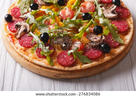 Hot Italian pizza with herbs, salami and vegetables close up on the table. horizontal  - stock photo