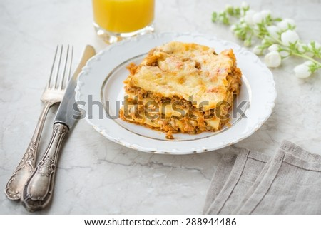 Hot Lasagna on a White Plate Homemade Delicious Food - stock photo