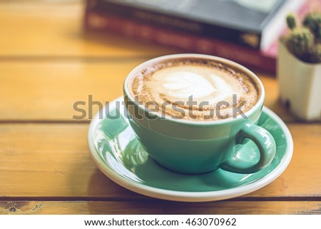 hot latte art in green cup on wooden table with book and tree.