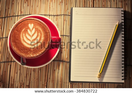 Hot latte coffee cup in a red cup on a table with notebook. - stock photo