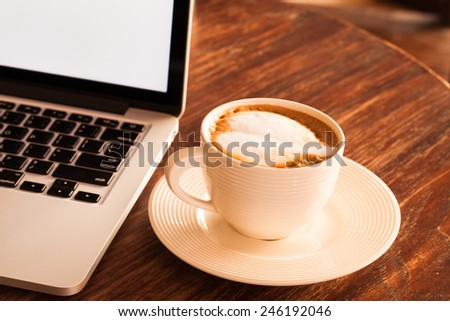 Hot latte coffee cup in a white cup on a table laptob in coffee shop. - stock photo