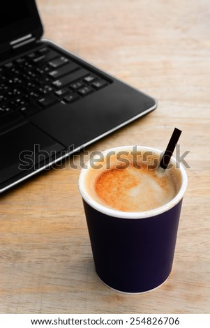 Hot latte coffee paper cup with computer notebook - stock photo