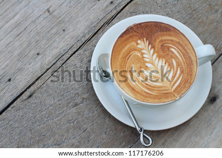 hot milk art coffee on wooden table - stock photo