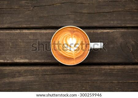 hot milk art coffee on wooden table - stock photo