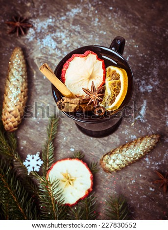 Hot mulled on dark wooden table with winter decoration,fir branch and cone - stock photo