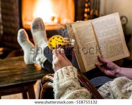 Hot mulled wine and book in woman hands. Relaxing in front of burning fire in the cold winter day.