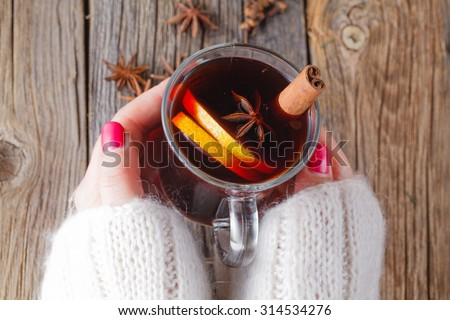 Hot mulled wine in female hands, spices on weathered wooden table. Sweet-home concept - stock photo