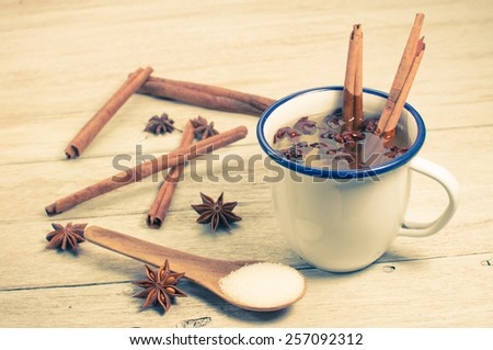 Hot mulled wine with anise and cinnamon on wooden table. - stock photo