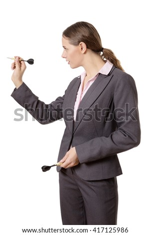 hot of a young, pretty business woman, wearing a suit, aiming a dart, ready to throw.  Isolated on white