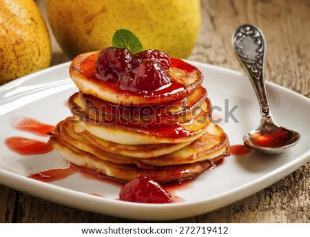 Hot pancakes with strawberry jam and mint leaves, selective focus - stock photo