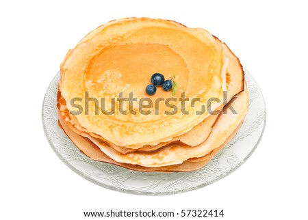 Hot pancakes with three small blueberry on glass plate