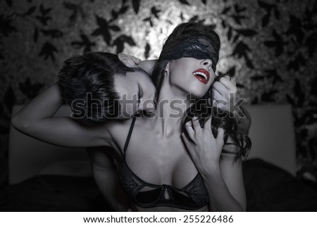 Hot passionate lovers at night, woman with lace eye cover and red lips - stock photo