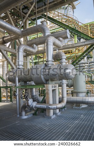 Hot piping in process area in factory - stock photo