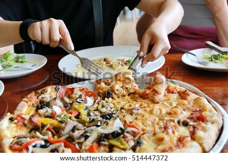 Hot pizza slice with melting cheese on a rustic wooden table. woman hand cut and slice pizza on wood table, pizza concept.