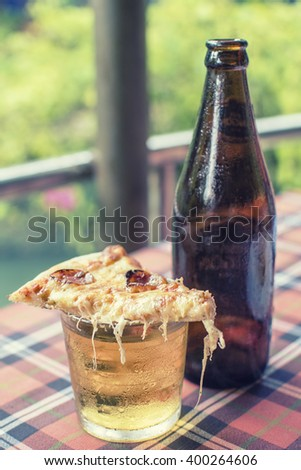 hot pizza with a cold beer on the table - stock photo