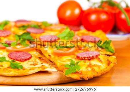 hot pizza with salami on background ripe tomato - stock photo