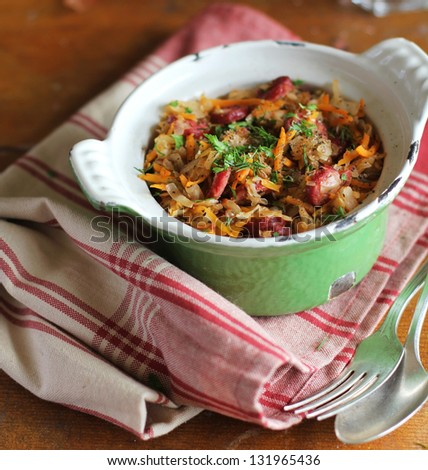 Hot pot of stewed white cabbage with carrots, tomato sauce, sausages and green lentil in a green sauce pan ready to serve - stock photo
