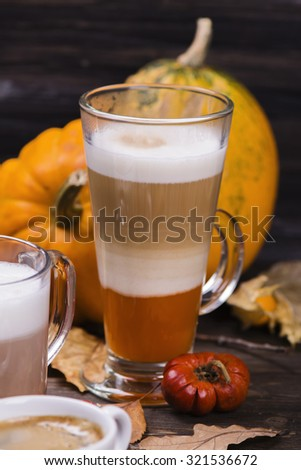 Hot pumpkin latte on wooden background. Selective focus - stock photo