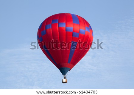 Hot red air balloon over blue sky.