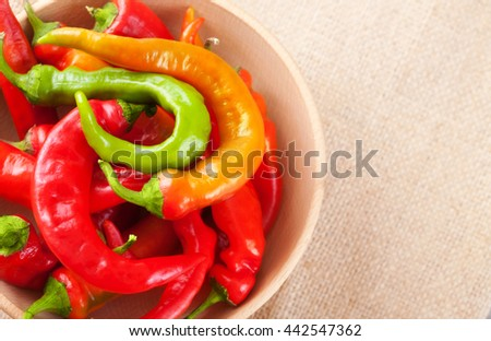 Hot red and green chili peppers in a bowl on a table, top view - stock photo