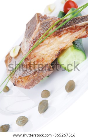 hot red beef meat steak on white plate with capers and tomatoes isolated over white background . shallow dof - stock photo