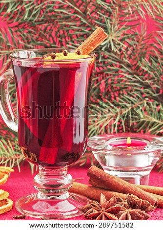 Hot red mulled wine  with christmas spices, orange slice, anise and cinnamon sticks, close up. - stock photo